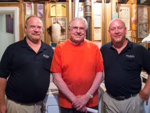 Three men standing next to each other smiling in a basement